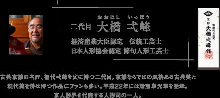 二代目 大橋 弌峰(おおはし いっぽう) 経済産業大臣認定 伝統工芸士 日本人形協会認定 節句人形工芸士 古典京雛の名匠、初代弌峰を父に持つ二代目。京雛ならではの風格ある古典美と現代美を併せ持つ作品にファンも多い。平成22年には瑞宝単光章を受章。京人形界を代表する人形司の一人。